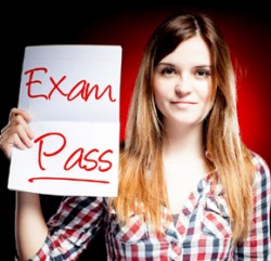 Student holding up paper which says `Exam Pass'
