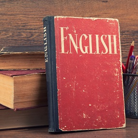 Books piled on top of one another next to a pen pot with a red book in front titled `English'.