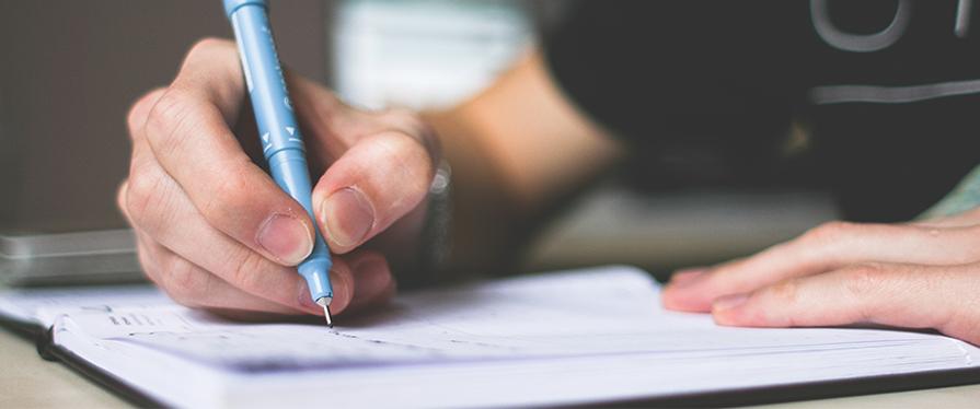 GCSE header image of mans hand writing