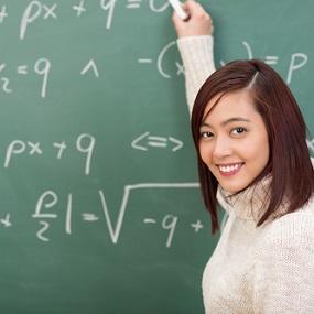 A level Maths and Mechanics Student writing on blackboard
