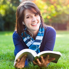 Student reading a Sociology GCSE Textbook in sunny field